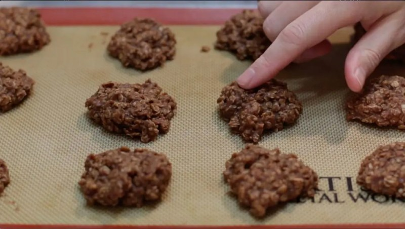 several finished no-bake chocolate oatmeal cookies on a baking sheet with a finger touching one.