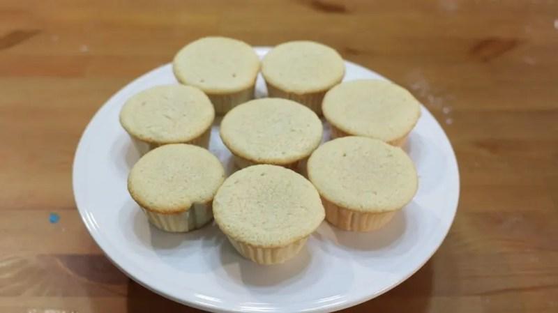 8 vanilla cupcakes on a white cake pedestal.