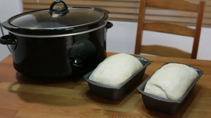 Two loaves of bread in bread pans next to a Crock Pot
