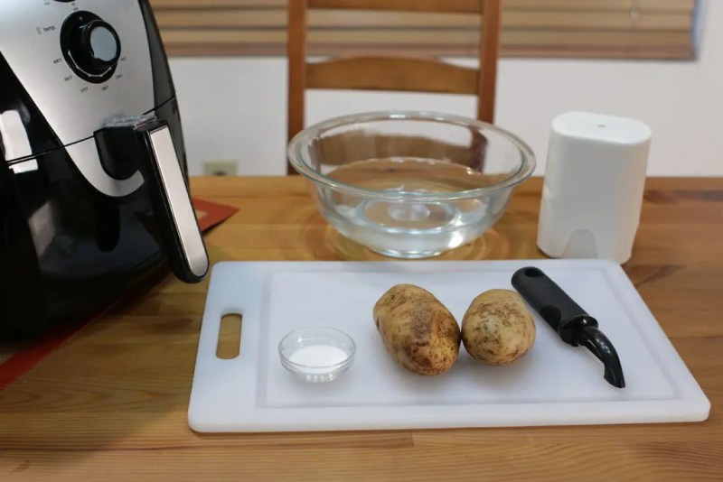 Black and silver air fryer with glass bowl of water, potatoes, and french fries cutter.