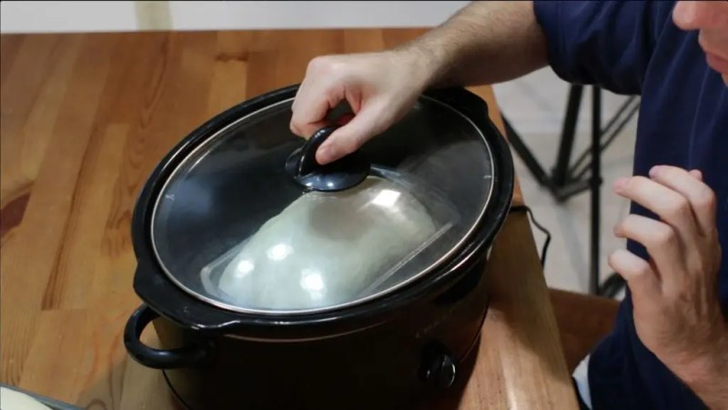 Bread loaf inside a crock pot with the lid covering it.
