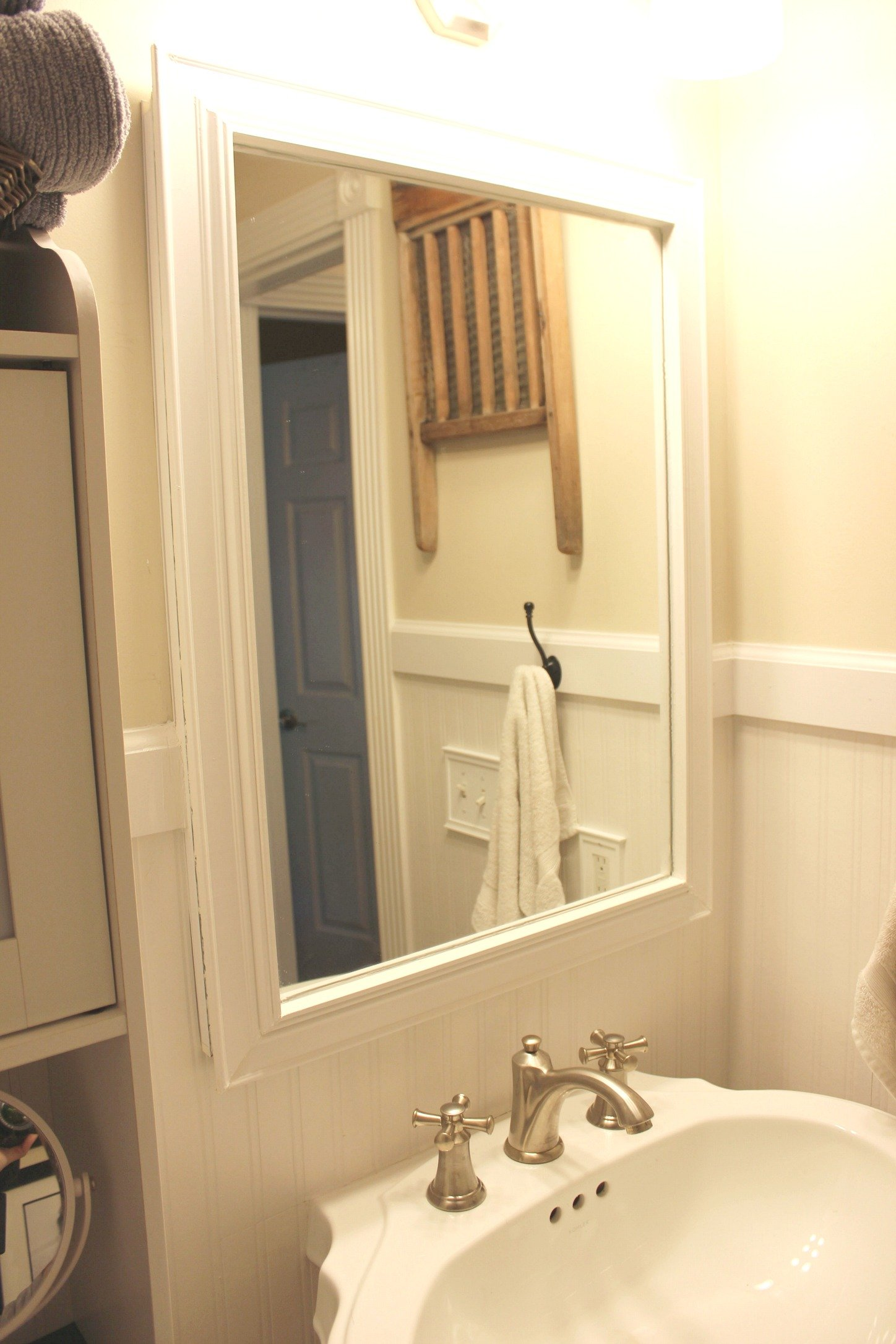 Frame a small bathroom mirror with trim and adhesive caulk to make ...
