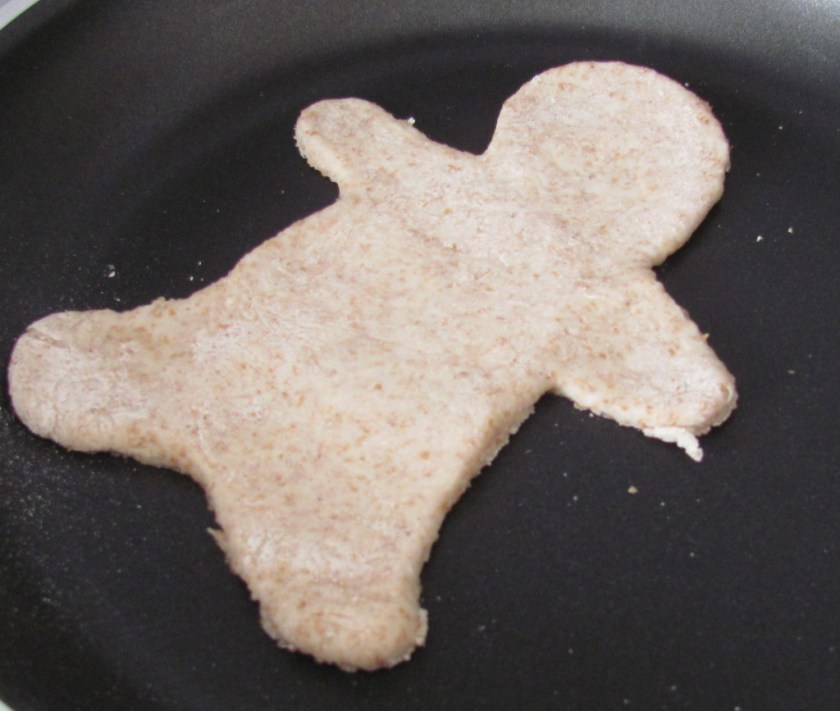 raw dough of the gingerbread man shaped roti in the pan before cooking