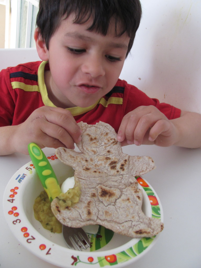 boy eating gingerbread man shaped roti with daal