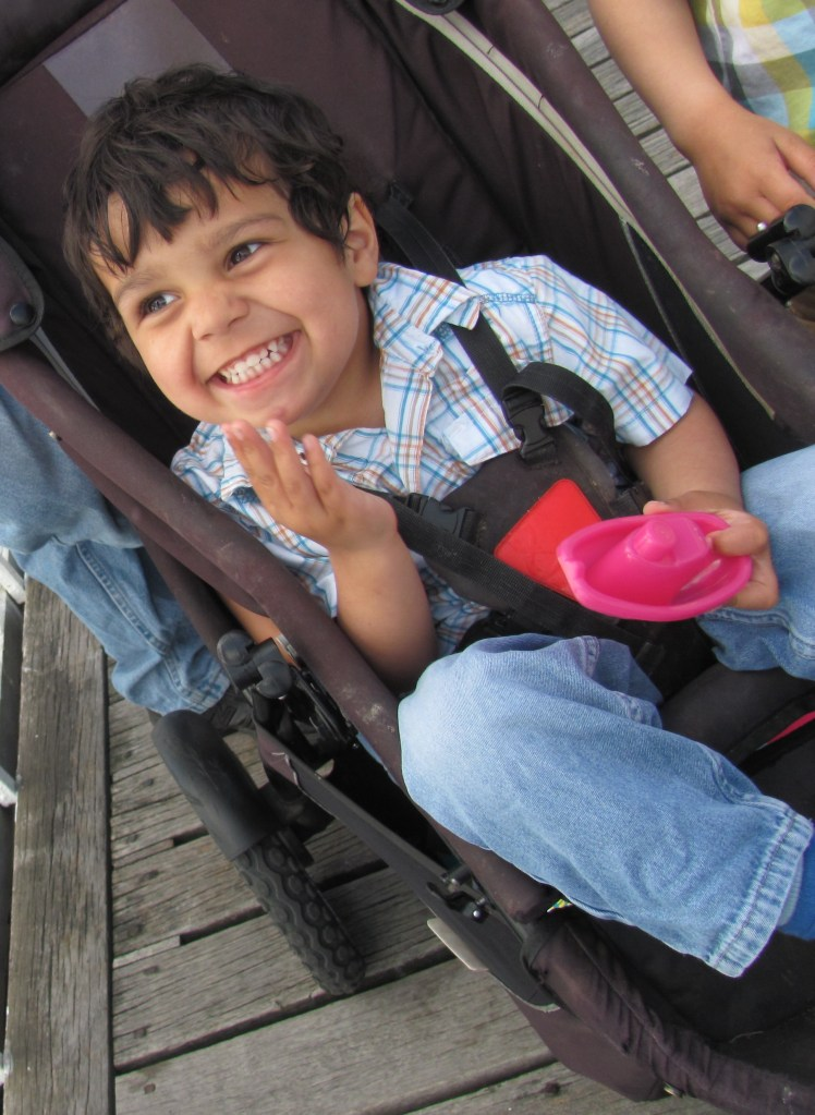 smiling grinning happy toddler 3 year old little boy in a buggy stroller pushchair at the seaside