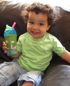 toddler in a green tshirt with a sippy cup drinking chocolate milk from a straw