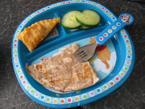 toddler dinner, in blue compartmentalised plated with sections, in a plastic toddler plate. roti, keema pastry and cucumber