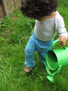 baby toddler with green watering can