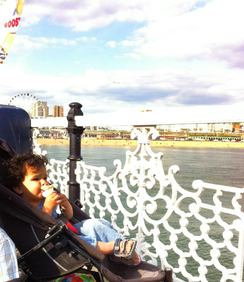baby toddler on brighton pier eating an ice cream looking at the sea