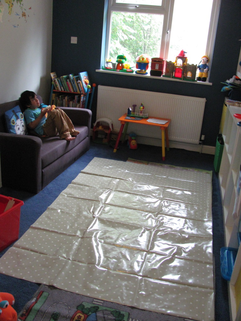 oil cloth mat in the playroom for messy play