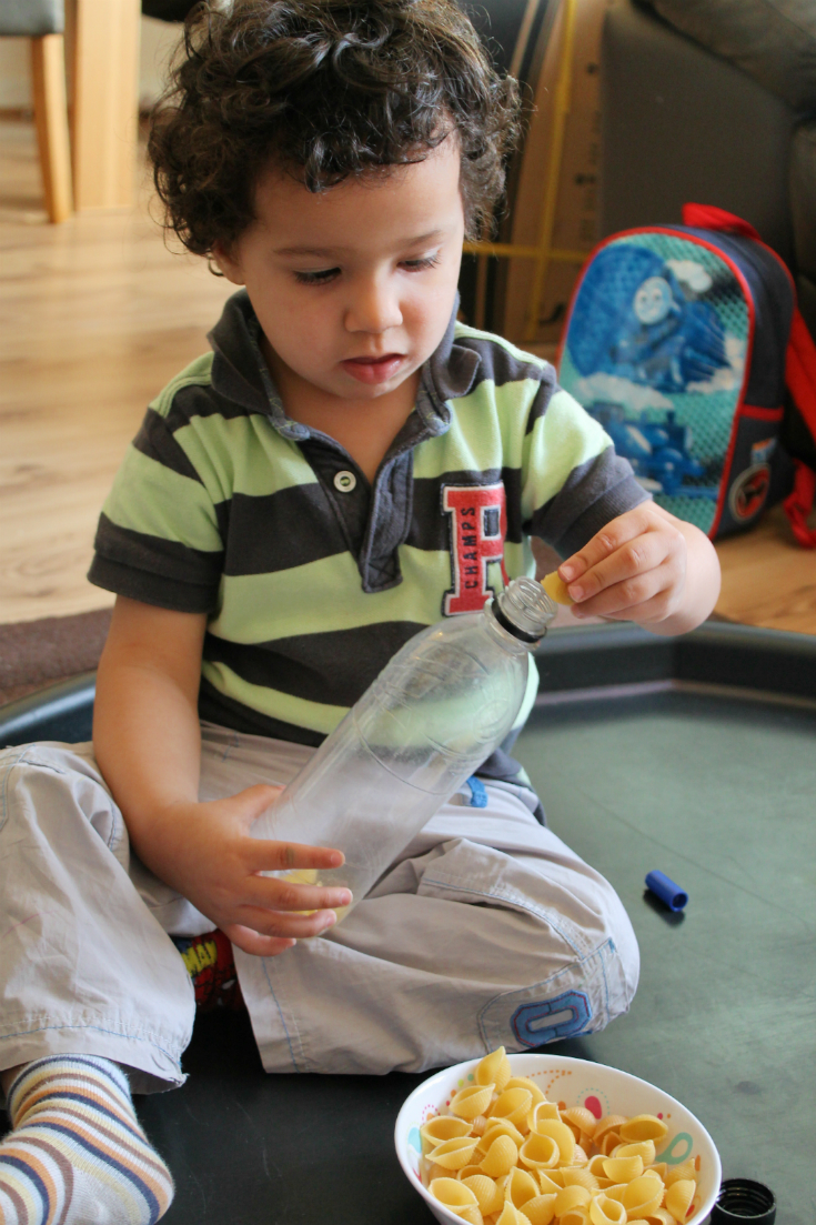 filling home made musical shakers for toddlers