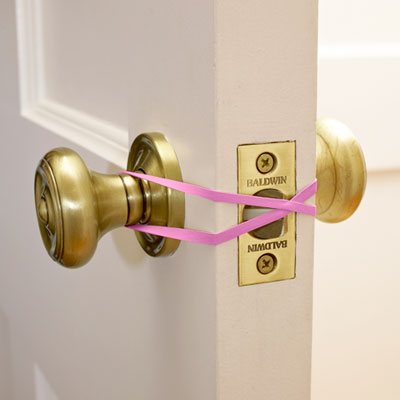 parenting hack prevent doors from closing with a rubber band