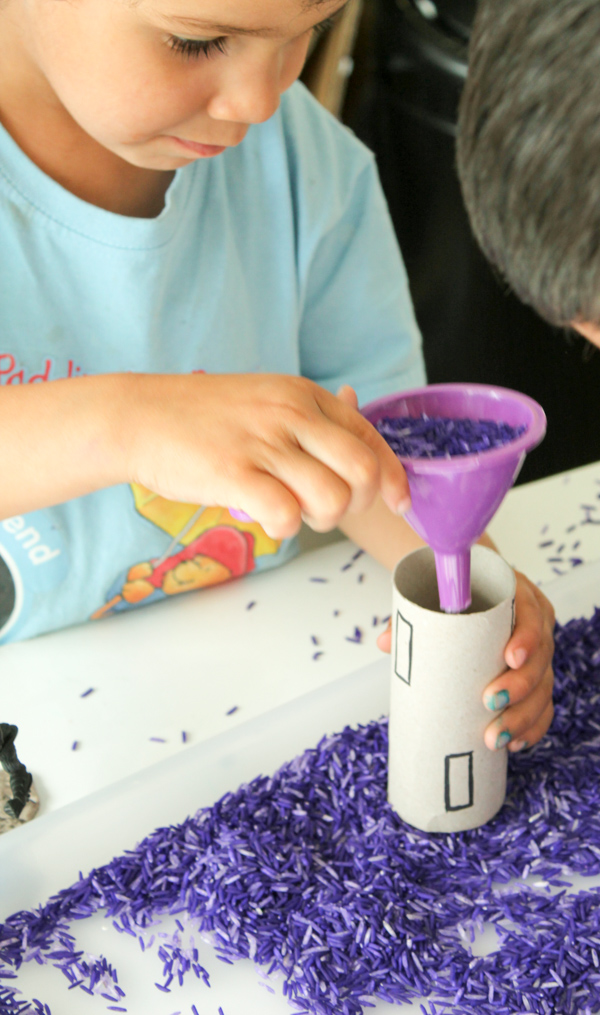 sensory play with coloured rice and funnel