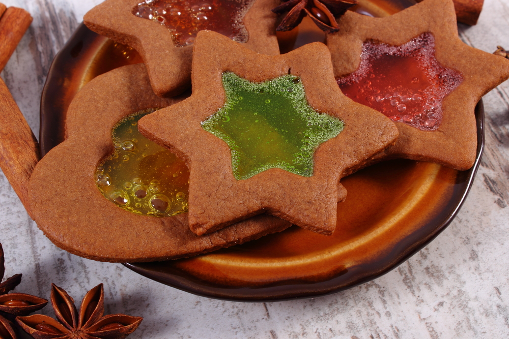 Fresh homemade decorated stained glass gingerbread, Christmas cookies on plate on old white wooden background, christmas time