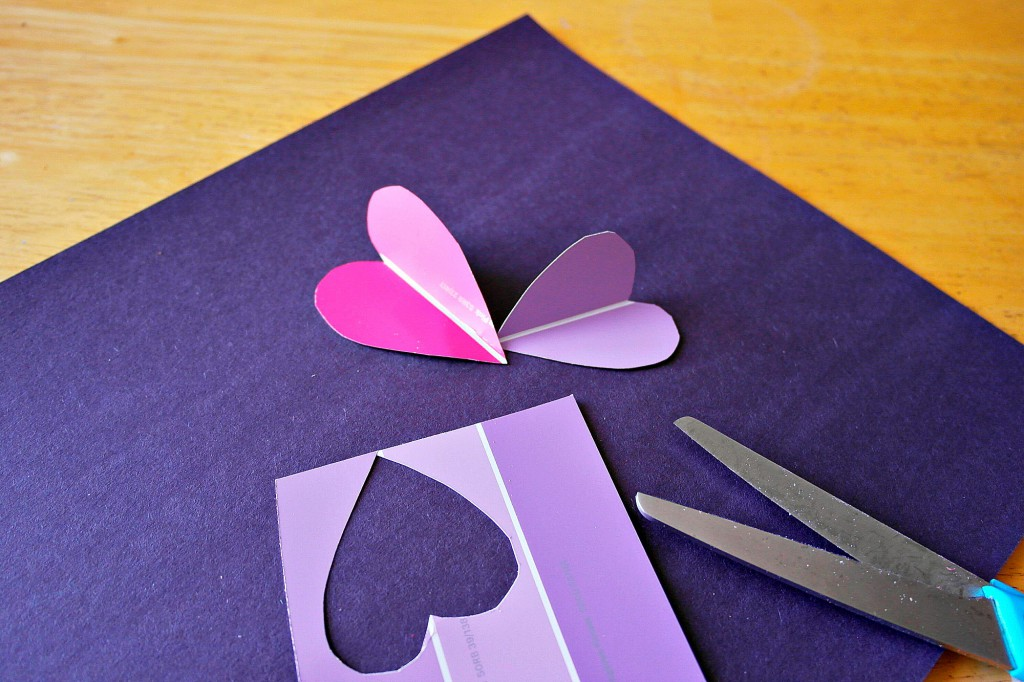 cutting hearts from paint samples, to make a flower