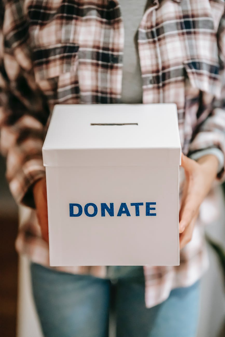 crop anonymous person showing donation box