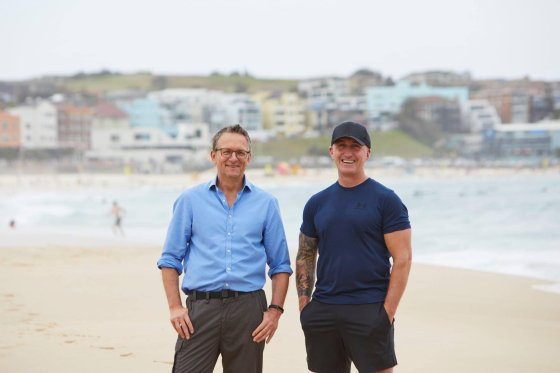 Dr Michael Mosley, left, and exercise physiologist Ray Kelly, standing on Bondi Beach. The image is a still for their program on SBS TV.