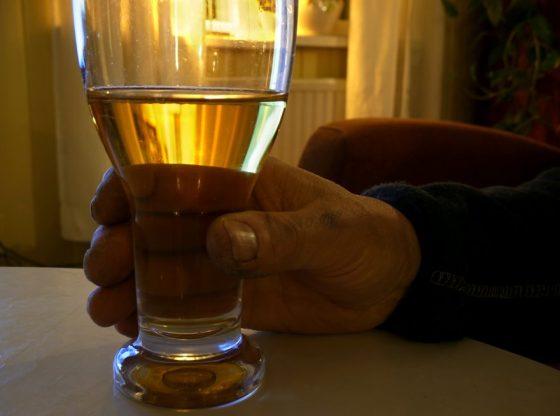 A man's hand holding glass of alcohol. Photography by Santeri Viinamäki/Wikipedia