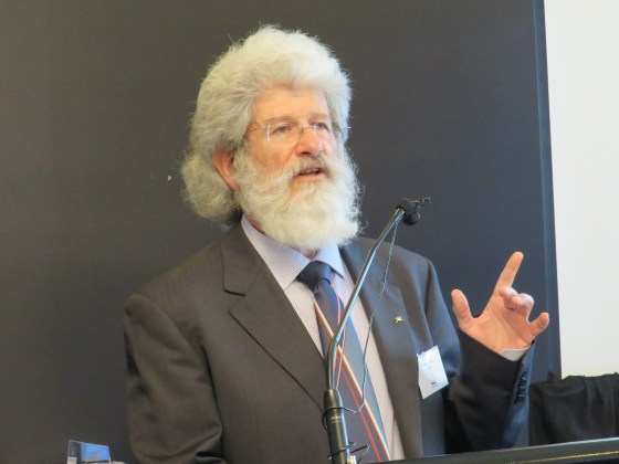 Dr Peter Tait gestures while speaking at a lectern.
