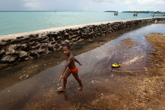 A boy pulls a toy on a string beside a sea wall. This photo of Saibai island in the Torres Strait was taken by Brad Marsellos and posted to Flickr.