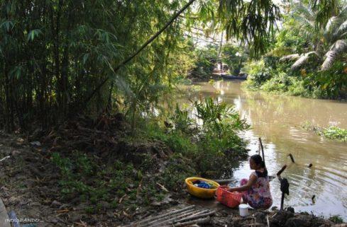 donna lava panni nei canali del delta del Mekong
