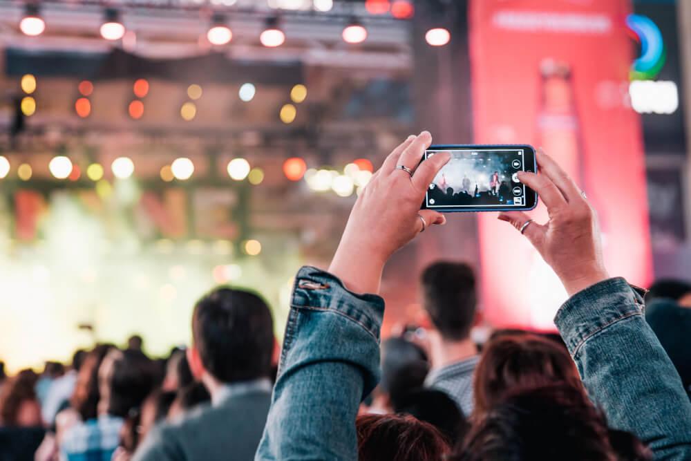 in het publiek van een festival of concert films en foto's maken