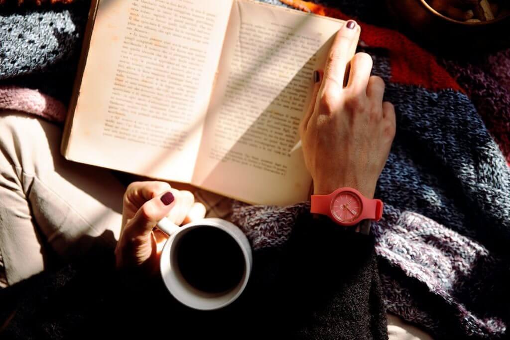 bovenaanzicht van een persoon met een boek op schoot, een beker koffie in de hand en een opvallend roze horloge aan de pols