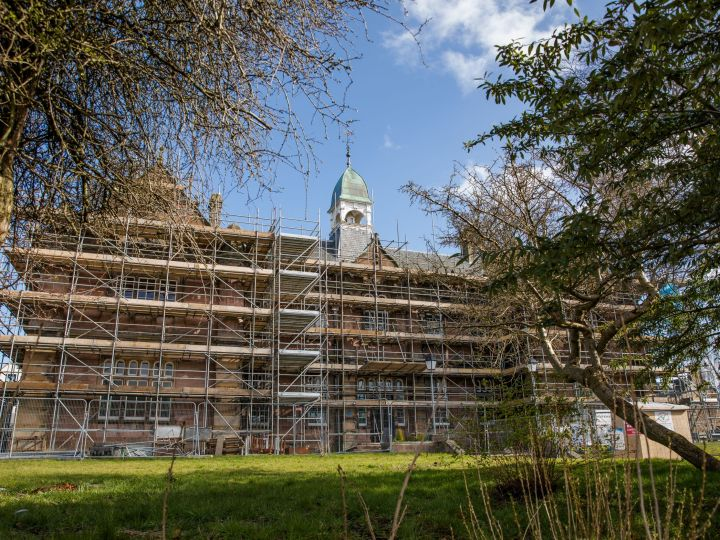 The grand Victorian Midmills Buildings, home of Inverness Creative Academy, peer through trees clad in scaffolding ready for construction