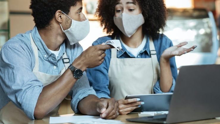Financial problems in family small business during covid-19 pandemic. Sad young african american couple in aprons and protective masks gesturing and talking about bills and work with laptop in cafe