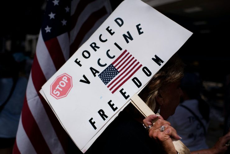 Anti-vaccine rally protester holds a sign saying 'Stop Forced Vaccine' above an American flag.