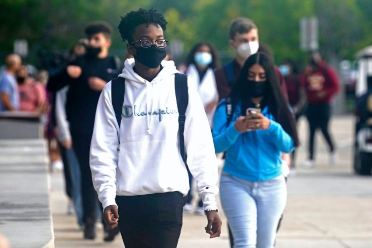 Students in face masks walk to school on the street.