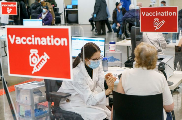 A woman administers a vaccine to another woman, seated, from behind