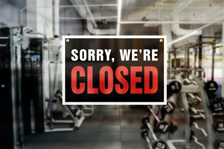 A sign reads 'Sorry, we're closed' on the window of a workout room