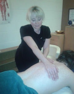 A photograph  of Vivienne providing a massage treatment