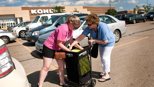Customers pull a dinnerware set from a shopping cart outside of a Kohl's store in Peru, Illinois.