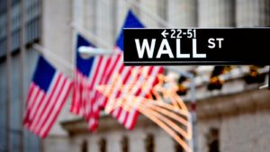 Wall Street street sign pictured in front of several American flags representing American stocks