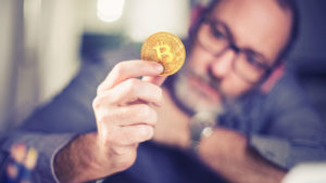 man in glasses holding a coin that has the Bitcoin (BTC-USD) logo