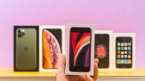 Detailný záber na rôzne telefóny Apple (AAPL) pred fialovým pozadím.