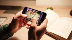 A close-up shot of hands playing a video game on a mobile phone.