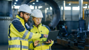 Ingegneri in giacche gialle e elmetti che guardano un laptop in un'officina