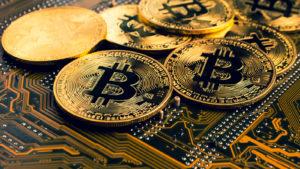 Token Bitcoin su una scheda madre che rappresentano BTC.
