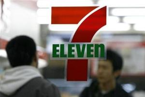 Man walks behind the logo of a 7-Eleven convenience store in Tokyo