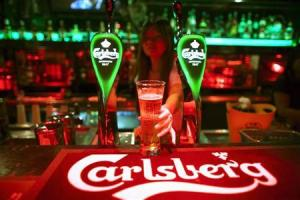 A bartender serves a glass of Carlsberg beer at a bar in Kuala Lumpur