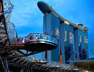 People stand on a platform of the Helix Bridge leading the soon to be opened Marina Bay Sands casino in Singapore