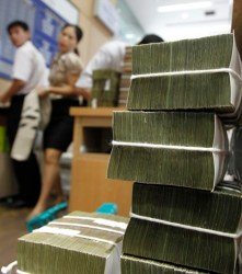 A staff employee carries a bag of money behind bundles of Vietnamese dong banknotes at a branch of BIDV in Hanoi
