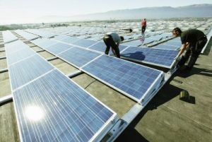 Workers install solar panels on the roof of the Palexpo Exhibition Center in Geneva