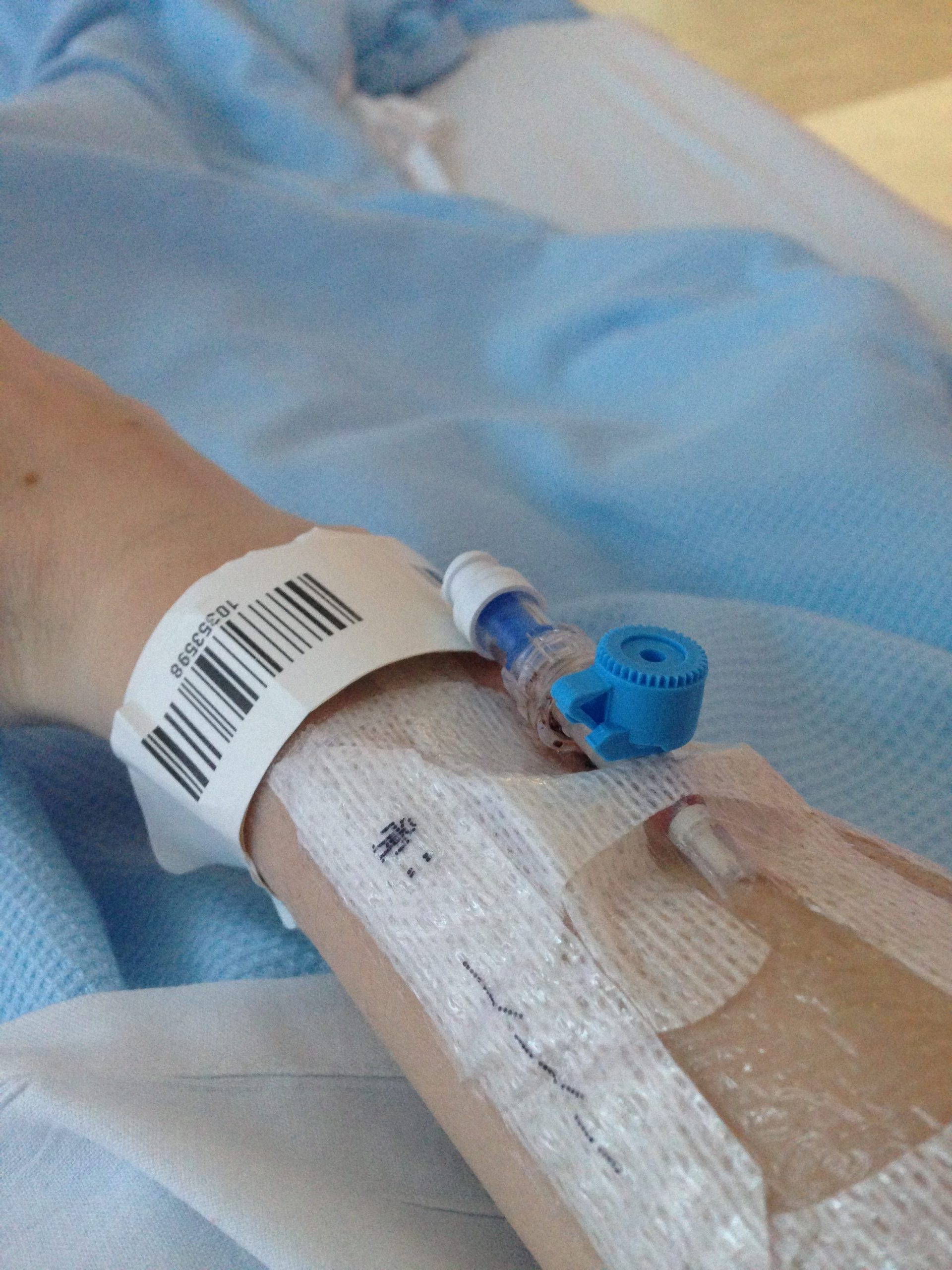 A close-up of my right arm with the hospital tag around my wrist and an IV in my arm.