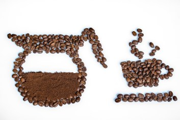 An image of a coffee pot and steaming cup of coffee made out of coffee beans spread on a white surface.