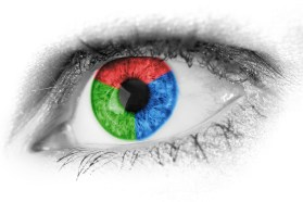 A close up of an eye with a  multicoloured iris in green, red and blue.