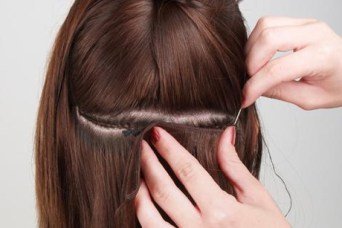 The back of a brunette's head showing another lady separating the hair line to place in an extension.